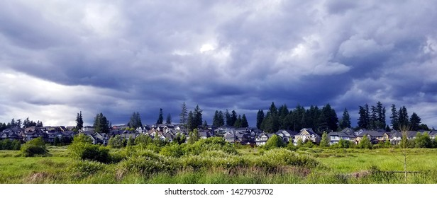 Wide shot of neighborhood in Surrey BC, Canada, with dark stormy skies overhead.