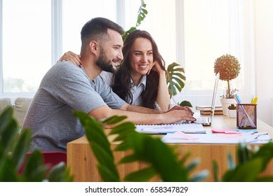 Wide shot of nice man and woman surfing in laptop while sitting at table