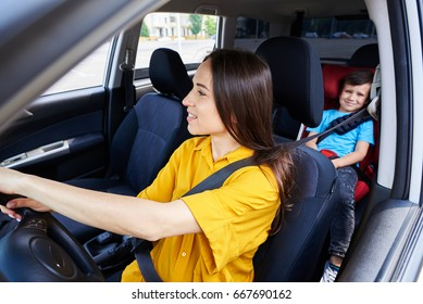 Wide shot of nice woman driving car with son sitting in baby seat