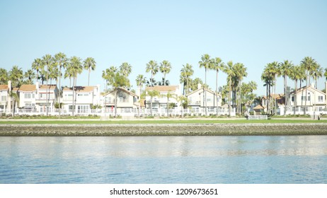 Wide shot of oceanfront homes and palm trees under a sunny sky