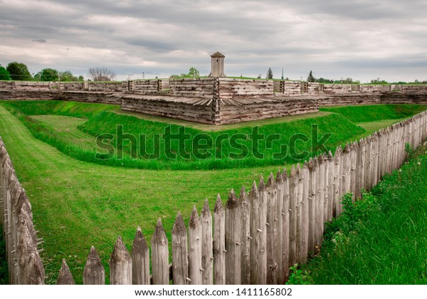Wide shot of the old revolutionary war Fort Stanwix in Rome New York.  The fort is surrounded by a wooden picket fence and trench.