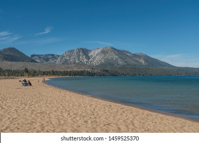 A wide shot of people sitting near the LakeTahoe shore with a mountain in the distance at California