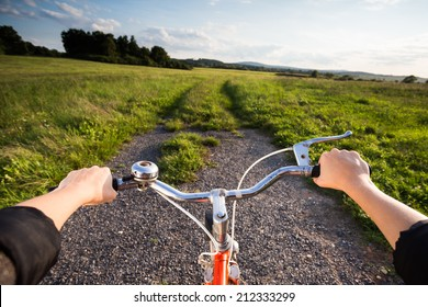 Wide shot of retro orange bicycle at sunset in countryside. Active summer. Woman biking in meadow at sunset. View from bikers eyes.