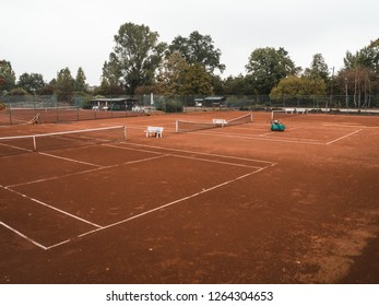 Wide shot of a rural, abandoned tennis court in autumn