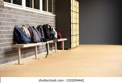 wide shot of school bags back packs sitting on a bench chair outside a grey brick class room with outdoor lockers in background. no students.