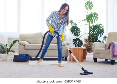 Wide shot of slim woman cleaning with vacuum cleaner carpet