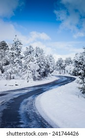 A wide shot of a small two lane road running through a winter landscape.