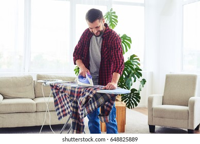 Wide shot of smiling dark-haired male ironing attentively clothes on ironing board
