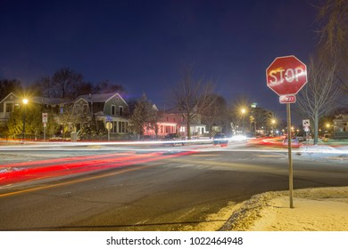 """A Wide Shot of A """"Stop"""" Sign Right Justified with Street Traffic at Night in Long Exposure"""