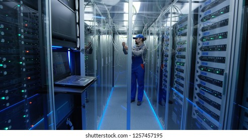 Wide shot of a technician working at a data center