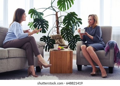 Wide shot of two women communicating while drinking coffee in living room
