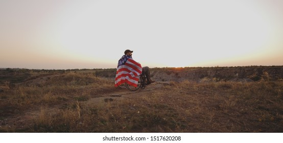Wide shot of a wheelchaired american soldier watching sunset on a meadow