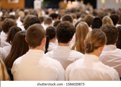 Wide shot of whole high school assembly formal presentation. Students in smartly dresses unform listening attentively. College hall education theme. Male student focus from behind