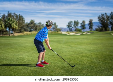 Wide shot of a young boy about to tee off at a beautiful golf course in Rancho Mirage, California