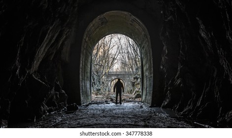 Wide silhouette view of a lone survivor emerging from entrance or exit of an abandoned cave tunnel with an apocalyptic feel and dark cinematic grunge effect.