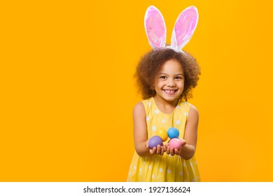 A wide smiling african girl in sunny orange dress with rabbit ears on her head with painted eggs in her hands. on a yellow background.