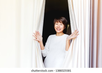 Wide smiling beautiful asian woman opens curtains on window. Young happy woman among textile folds of drapery.