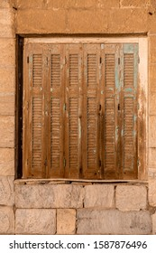 Wide square window with closed shabby retro brown wooden shutters in the sunlight, brick wall texture contour