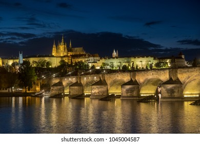 Wide static blue hour shot of Charles Bridge and Prague Castle at dusk. The bridge and castle are lit up