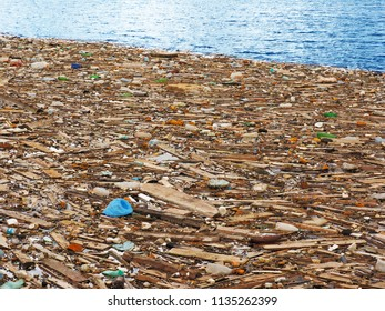 Wide strip of household and construction waste along the coastline of blue sea
