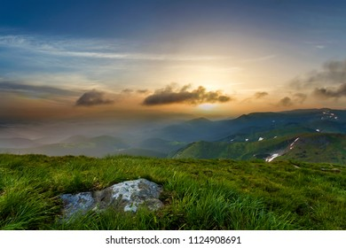 Wide summer mountain view at sunrise. Glowing orange sun raising in blue cloudy sky over green grassy hill with big rock and distant mountain range covered with morning mist. Beauty of nature concept.