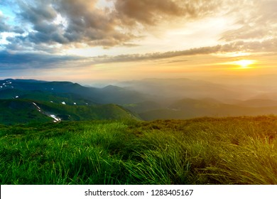 Wide summer mountain view at sunrise. Glowing orange sun raising in blue cloudy sky over green grassy hill soft grass and distant mountain range covered with morning mist. Beauty of nature concept.
