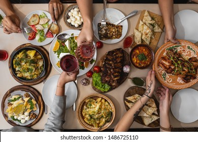 wide and tasty table covered with delicious Ukrainian cuisine on which sits a large family or friends their hands at the table during meals
