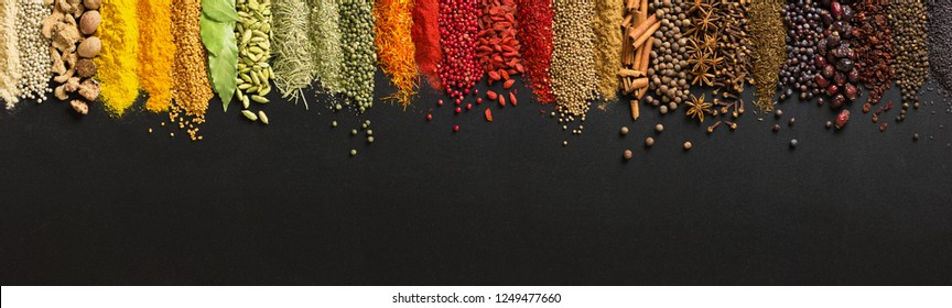 Wide variety spices and herbs on background of black table, with empty space for text or label.