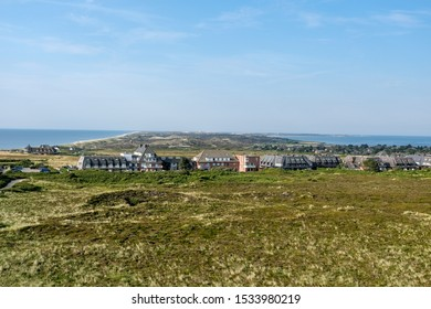 Wide view from above of the northern half of the island of Sylt, with nature reserve, dune landscape, houses and hotels with thatched roof and the sea on both sides