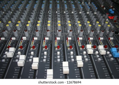A wide view of all the controls on a large mixing board, including faders and knobs.