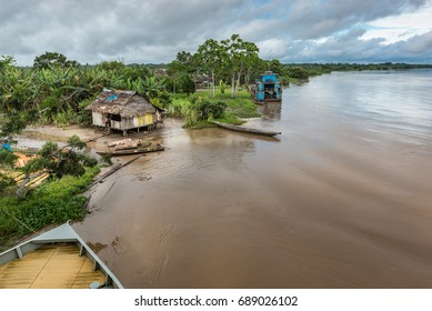 Wide view of Amazon shack and large blue boat on river with tip of tourist boat in foreground