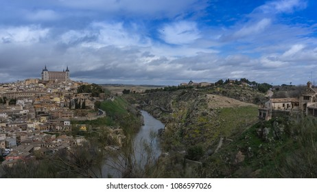 Wide view of the city of Toledo in Spain with the Alcazar on the left, monastery on the right and Tajo river in the center on a winter afternoon