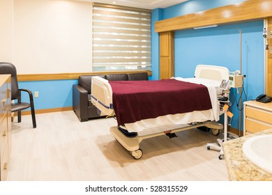 Wide view of an empty bed in a fully equipped and modern hospital room