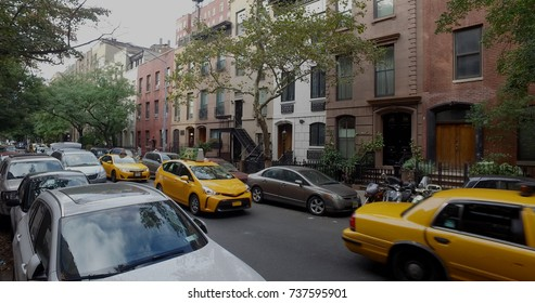 Wide view exterior shot of a typical generic New York City block with apartment buildings yellow taxi cab traffic and parked cars lining side of street.