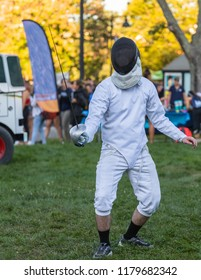 Wide view of a fencing athlete on a green field