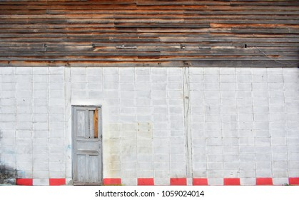 Wide view flat textured image of old dirty blocks concrete and a half wooden flat wall with old wooden grey door for vintage background concept