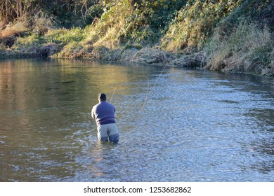 Wide view of a fly fisherman standing in a shallow creek wearing hip-waders while casting his line across the water.