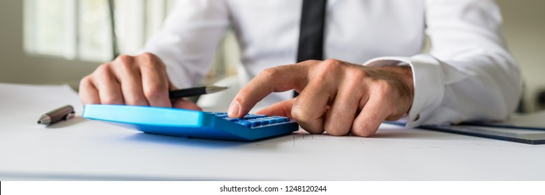 Wide view image of business engineer sitting at his office desk working on a project calculating numbers using a calculator.