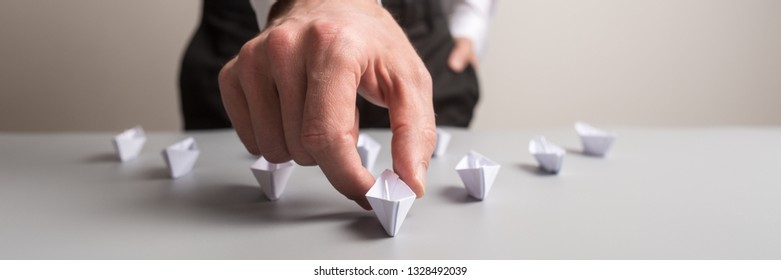 Wide view image of business executive holding the leading paper made boat of a group of many in a conceptual image of business leadership.