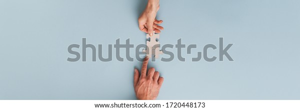 Wide view image of business partners, businessman and businesswoman, joining two blank matching puzzle pieces. Top view over blue background.