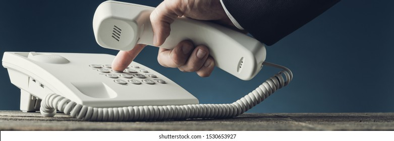 Wide view image of businessman dialing telephone number on white landline phone while holding a handset. Over navy blue background.