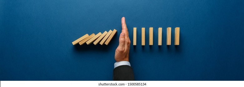 Wide view image of businessman hand stopping collapsing dominos in a conceptual image. Top view over navy blue background.
