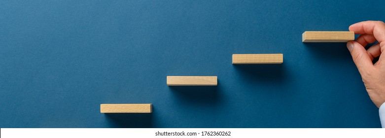 Wide view image of businessman hand building stairway of wooden blocks over blue background in a conceptual image of strategy and promotion.