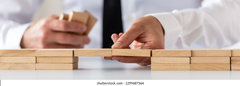 Wide view image of businessman making a bridge of wooden pegs in a conceptual image of business merger and challenge.