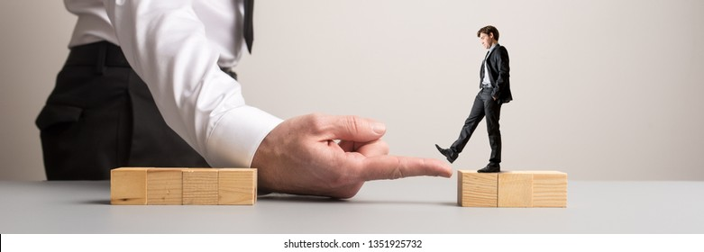 Wide view image of businessman placing his hand between two blocks of wooden cubes for another businessman to walk across in a conceptual image.