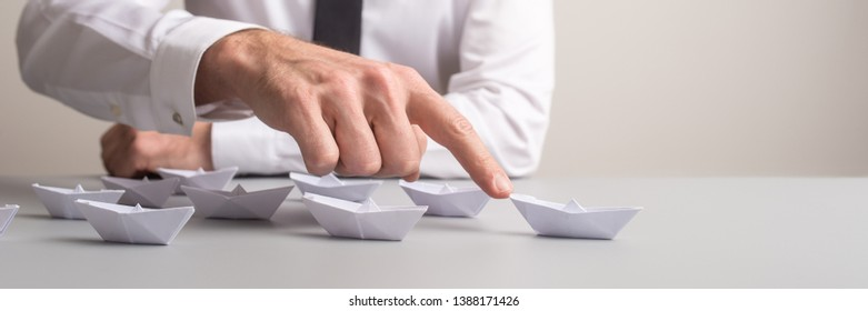 Wide view image of businessman pushing forward one of many paper made origami boats in a conceptual image of excellence and promotion.