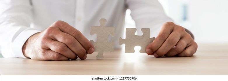 Wide view image of a businessman sitting at his desk holding two matching puzzle pieces.
