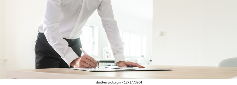 Wide view image of businessman standing at his office desk leaning forward as he signs an investment document in a folder.