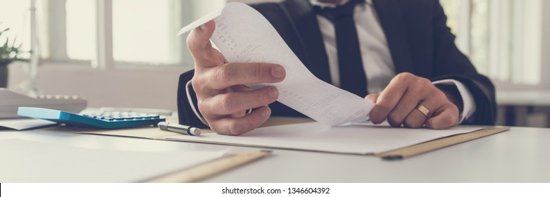 Wide view image of financial adviser sitting at his desk looking at receipt while making an annual balance report.