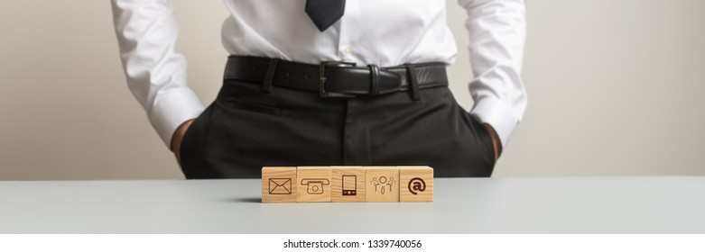 Wide view image of five wooden cubes with communication symbols on them placed in a row on white office desk with businessman standing in background.